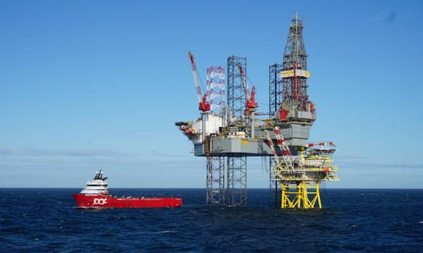 Tolmount platform with drilling rig and a stanby vessel - Credit: Harbour Energy