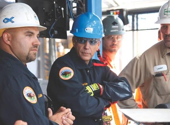 Джош Лэднер (слева), руководитель отдела инспекций скважин в округе BSEE Хума, обсуждает процесс инспекции на шельфе с директором BSEE Скоттом Анхель (в центре). (Фото: BSEE)