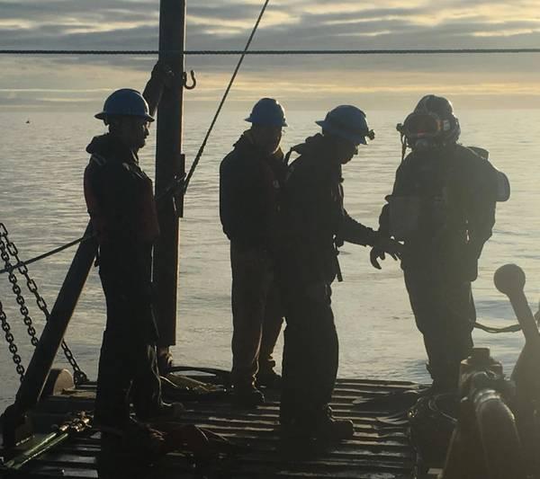 Comenzando al amanecer, los buzos comienzan una serie de inmersiones durante mareas flojas para asegurar las mangas divididas compuestas de Snap Wrap a las áreas dañadas de una tubería en Cook Inlet, Alaska. (Foto cortesía de ClockSpring | NRI)