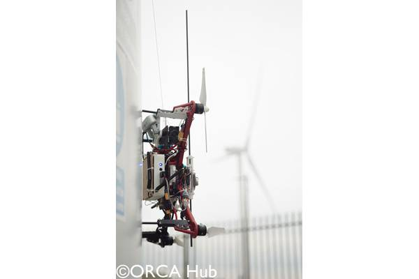 The Imperial College London drone demonstrating autonomous UAV sensor placement on a wind turbine at the ORE Catapult facility in Blyth. The drone is equipped with a winch-tethered magnet and passive wheels capable of perching on, and sliding along, both vertical and horizontal surfaces.